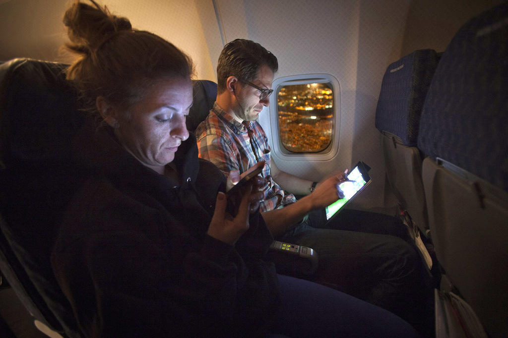 People use their smart devices on an American Airlines airplane, which is equipped with Gogo Inflight Internet service, enroute from Miami to New York