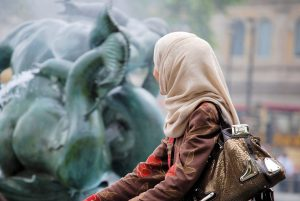 Muslim woman looks at statues