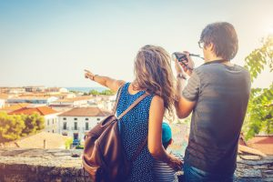 A couple with a camera looking at a city view